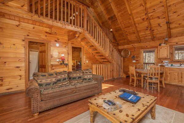 Sofa and dining room and kitchen at Smoky Bears Creek, a 2 bedroom cabin rental located in Pigeon Forge