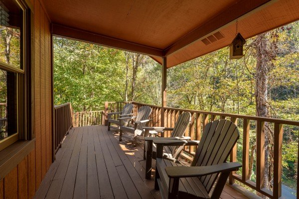 Adirondack chairs on a covered deck at Rustic Retreat at Shagbark, a 2 bedroom cabin rental located in Pigeon Forge