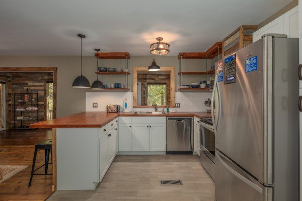 Kitchen with stainless appliances and a breakfast bar at Rustic Retreat at Shagbark, a 2 bedroom cabin rental located in Pigeon Forge