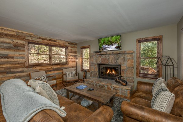 Living room with fireplace and TV at Rustic Retreat at Shagbark, a 2 bedroom cabin rental located in Pigeon Forge