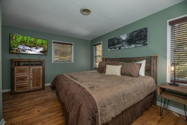Bedroom with a king bed, dresser, and TV at Rustic Retreat at Shagbark, a 2 bedroom cabin rental located in Pigeon Forge