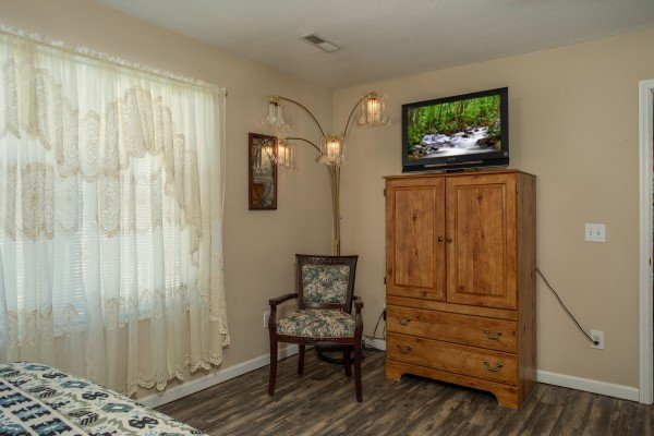 Armoire, TV, and chair in a bedroom at Peace at the River, a 3 bedroom cabin rental located in Pigeon Forge