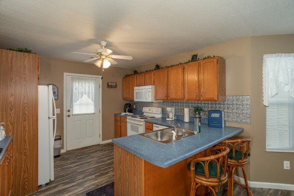 Kitchen with breakfast bar for two and white appliances at Peace at the River, a 3 bedroom cabin rental located in Pigeon Forge