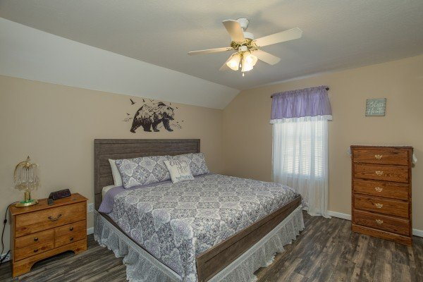 Bedroom with a king bed, dresser, and small dresser at Peace at the River, a 3 bedroom cabin rental located in Pigeon Forge