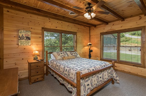 bedroom with wood bed and nightstand at amazing grace a 3 bedroom cabin rental located in pigeon forge