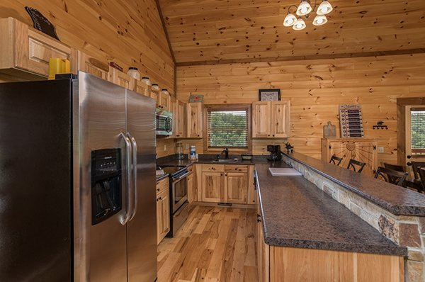 kitchen with seating at the bar top at amazing grace a 3 bedroom cabin rental located in pigeon forge