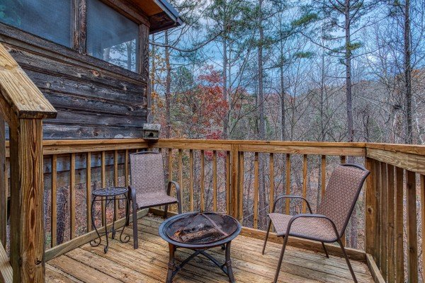 Fire pit and two chairs on an open deck at Hillside Hideaway, a 1 bedroom cabin rental located in Pigeon Forge