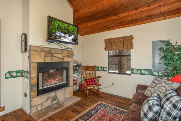 Den with see through fireplace and TV at Hillside Hideaway, a 1 bedroom cabin rental located in Pigeon Forge
