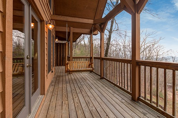 Swing on a covered deck at Valley View Lodge, a 3 bedroom cabin rental located in Pigeon Forge