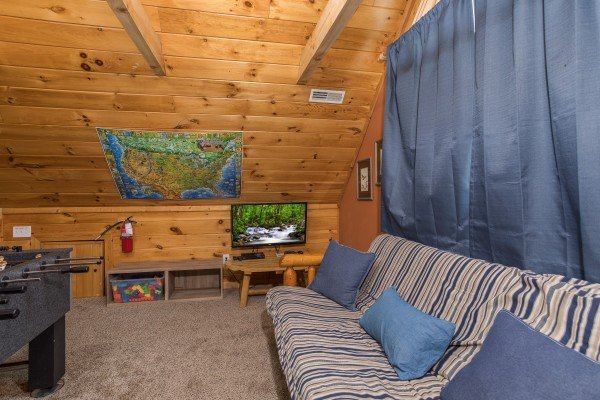 Loft space with a futon and TV at Valley View Lodge, a 3 bedroom cabin rental located in Pigeon Forge