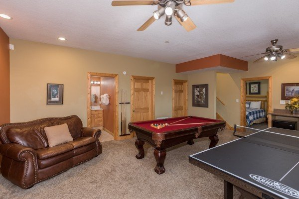 Leather sofa, pool table, and ping pong at Valley View Lodge, a 3 bedroom cabin rental located in Pigeon Forge