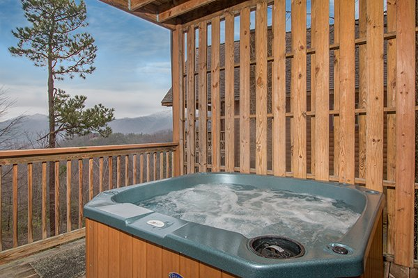 Hot tub on a covered porch with a privacy fence at Valley View Lodge, a 3 bedroom cabin rental located in Pigeon Forge