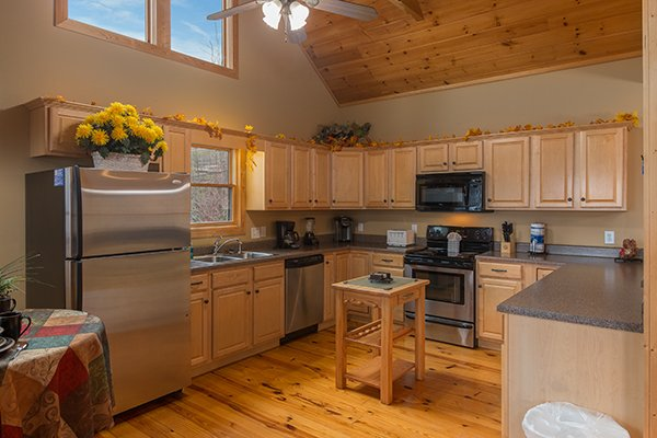 Kitchen with stainless appliances and a small island table at Valley View Lodge, a 3 bedroom cabin rental located in Pigeon Forge