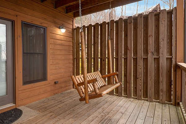 Swing on a covered porch with privacy fence at Valley View Lodge, a 3 bedroom cabin rental located in Pigeon Forge