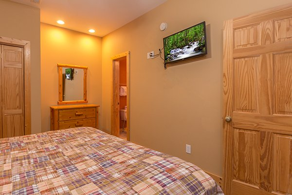 TV, dresser, and en suite bathroom at Valley View Lodge, a 3 bedroom cabin rental located in Pigeon Forge