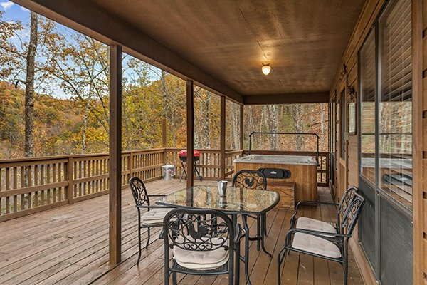 Hot tub and dining table for four on the covered deck at Papa Bear, a 3 bedroom cabin rental located in Pigeon Forge