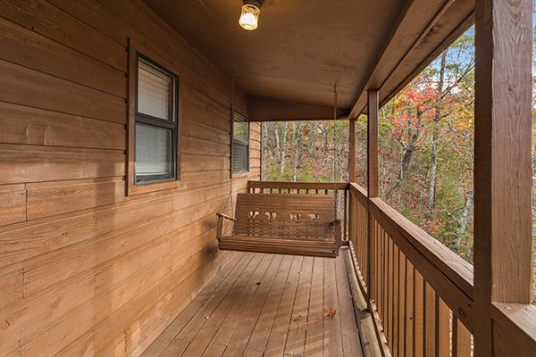 Porch swing on a covered deck at Papa Bear, a 3 bedroom cabin rental located in Pigeon Forge