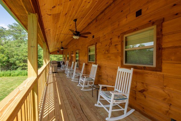 Covered porch with ceiling fans and white rocking chairs at Always Dream'n, a 6 bedroom cabin rental located in Pigeon Forge