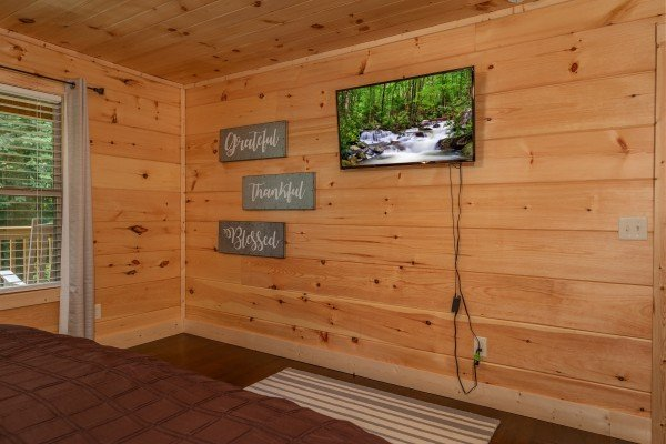 Wall mounted TV in a bedroom at Always Dream'n, a 6 bedroom cabin rental located in Pigeon Forge