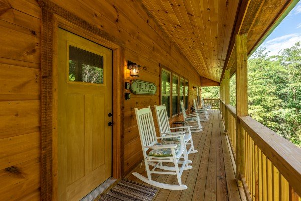 Covered front porch with white rocking chairs at Always Dream'n, a 6 bedroom cabin rental located in Pigeon Forge