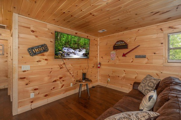 Large wall mounted TV in the game room at Always Dream'n, a 6 bedroom cabin rental located in Pigeon Forge