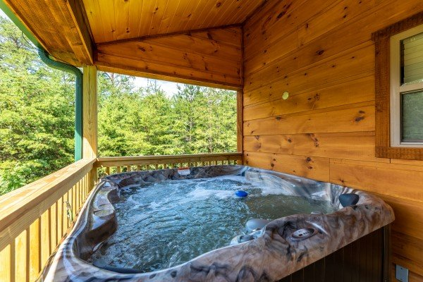 Hot tub on a covered deck at Always Dream'n, a 6 bedroom cabin rental located in Pigeon Forge