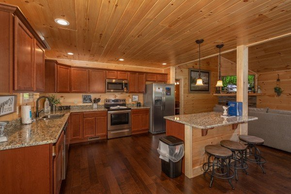 Kitchen with stainless appliances, granite counters, and bar seating for 3 at Always Dream'n, a 6 bedroom cabin rental located in Pigeon Forge