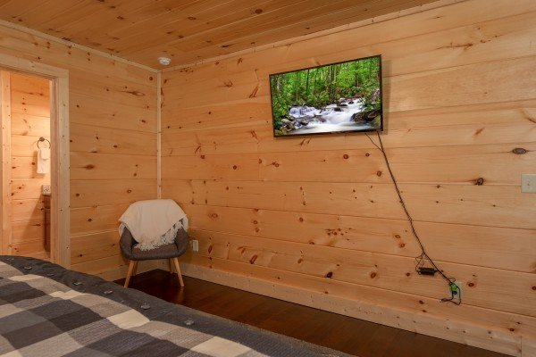 Chair and wall mounted TV in a bedroom at Always Dream'n, a 6 bedroom cabin rental located in Pigeon Forge
