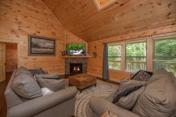 Vaulted living room with fireplace and TV at Always Dream'n, a 6 bedroom cabin rental located in Pigeon Forge