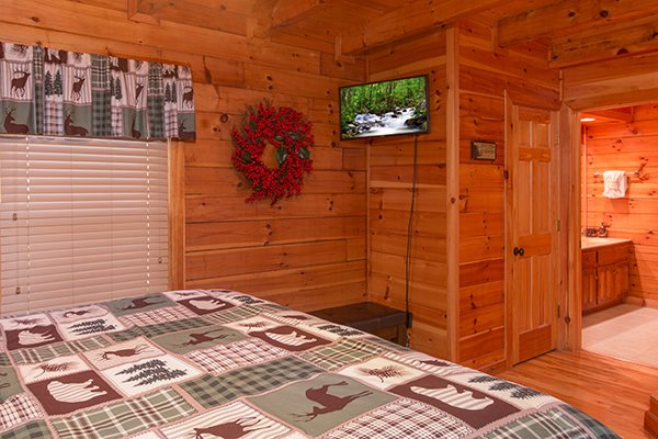 Bedroom with TV and en suite bath at Mountain Harvest, a 3 bedroom cabin rental located in Pigeon Forge