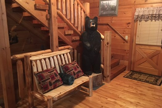 Wooden bench and bear statue at Mountain Harvest, a 3 bedroom cabin rental located in Pigeon Forge