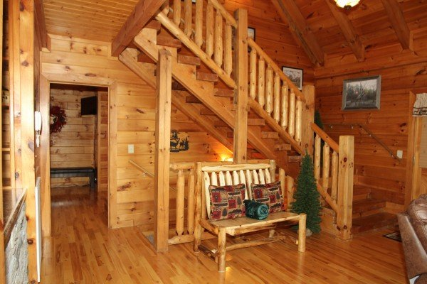 Bench near the stairs in the living room at Mountain Harvest, a 3 bedroom cabin rental located in Pigeon Forge
