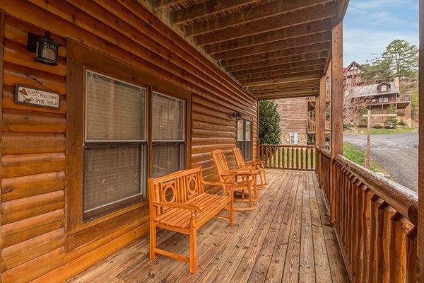 Front porch with rocking chairs and a bench at Mountain Harvest, a 3 bedroom cabin rental located in Pigeon Forge