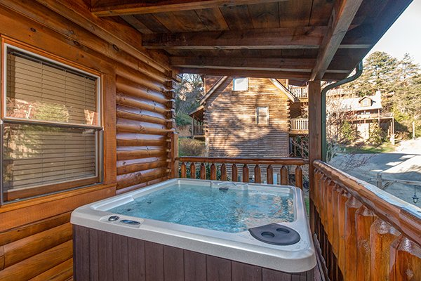 Hot tub on a covered deck at Mountain Harvest, a 3 bedroom cabin rental located in Pigeon Forge
