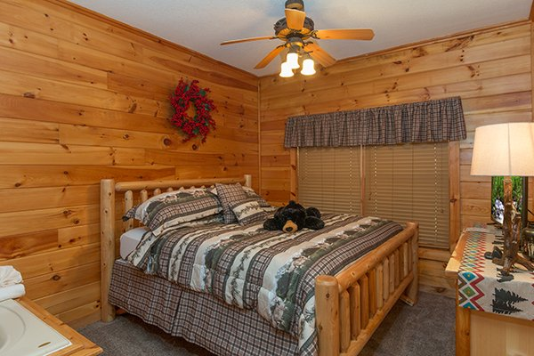 Bedroom with a king log bed at Mountain Harvest, a 3 bedroom cabin rental located in Pigeon Forge