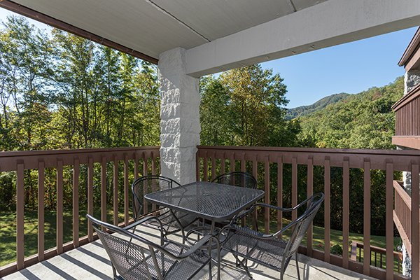 Dining space for four on the covered patio at High Alpine #204, a 2 bedroom cabin rental located in Gatlinburg