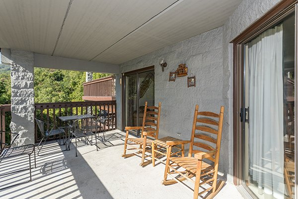 Rocking chairs and dining space for four on the patio at High Alpine #204, a 2 bedroom cabin rental located in Gatlinburg