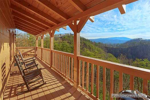 Covered deck with grill and rockers at Sunset Vista View, a 1 bedroom cabin rental located in Pigeon Forge