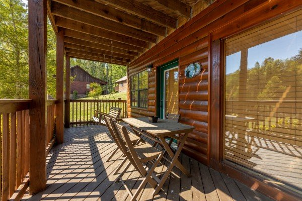 Deck dining table at Pool Side Lodge, a 6 bedroom cabin rental located in Pigeon Forge