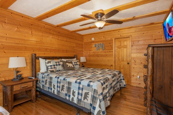 Bedroom with two night stands, lamps, dresser, and TV at Pool Side Lodge, a 6 bedroom cabin rental located in Pigeon Forge