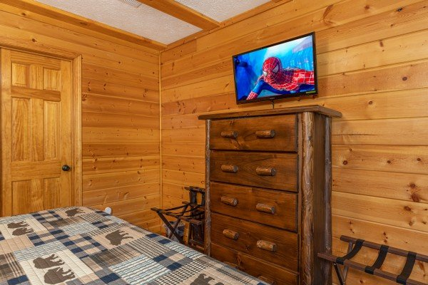 Dresser, two luggage racks, and TV in the bedroom at Pool Side Lodge, a 6 bedroom cabin rental located in Pigeon Forge