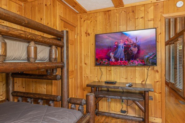 TV and console table in a bedroom at Pool Side Lodge, a 6 bedroom cabin rental located in Pigeon Forge
