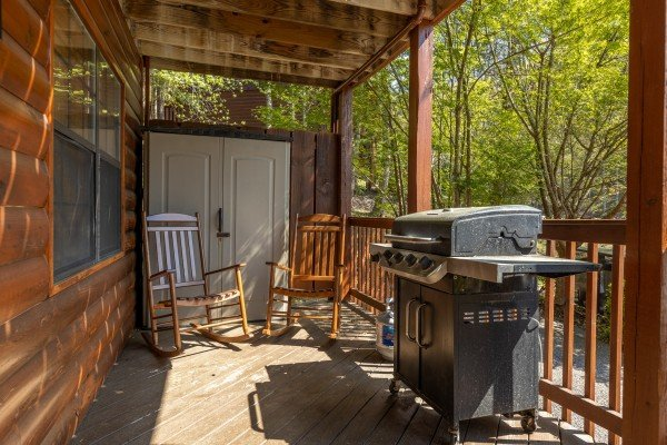 Grill and rocking chairs at Pool Side Lodge, a 6 bedroom cabin rental located in Pigeon Forge