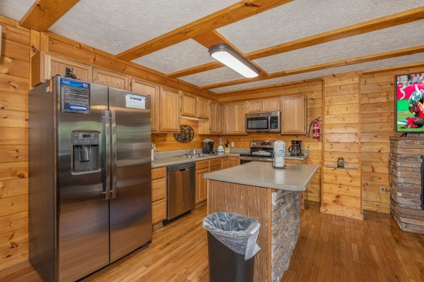 Kitchen with stainless appliances and a breakfast bar at Pool Side Lodge, a 6 bedroom cabin rental located in Pigeon Forge