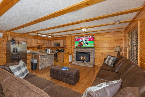 Living room with fireplace and TV at Pool Side Lodge, a 6 bedroom cabin rental located in Pigeon Forge