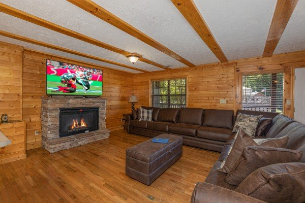 Fireplace, TV, and two sofas in the living room at Pool Side Lodge, a 6 bedroom cabin rental located in Pigeon Forge