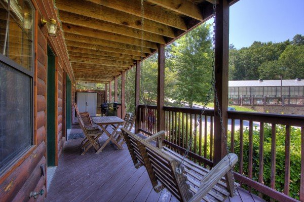 Swing and deck dining at Pool Side Lodge, a 6 bedroom cabin rental located in Pigeon Forge