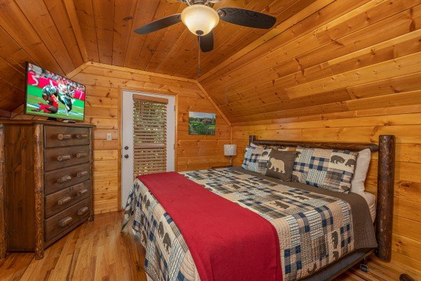 King bed, dresser, TV, and deck access in a bedroom at Pool Side Lodge, a 6 bedroom cabin rental located in Pigeon Forge
