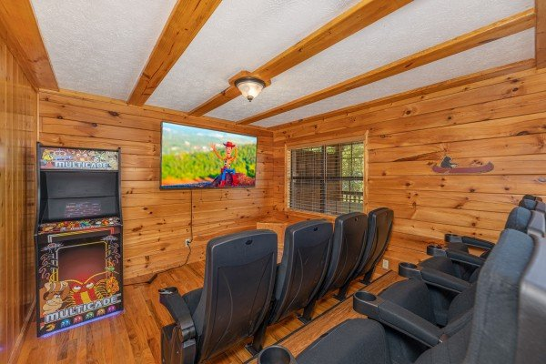Theater room and arcade game at Pool Side Lodge, a 6 bedroom cabin rental located in Pigeon Forge