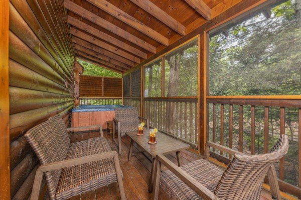Covered deck with wicker seating and a hot tub at Location Location Location, a 1 bedroom cabin rental located in Pigeon Forge
